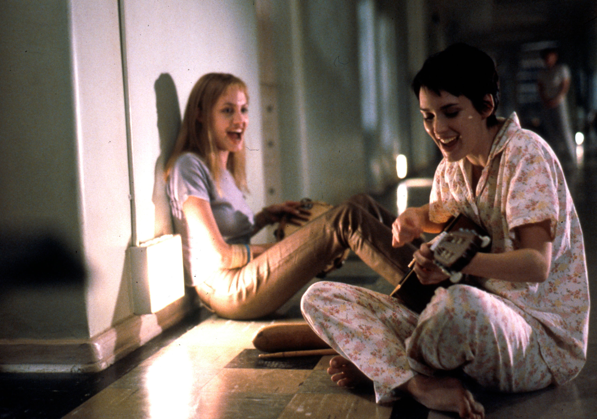 Apr 20, 2000; Hollywood, California, USA; After friend and fellow patient Polly lands herself in solitary, ANGELINA JOLIE (left as Lisa) and WINONA RYDER as Susanna Serenade her in 'Girl Interrupted'. Mandatory Credit: Photo by Suzanne Tenner/Columbia TriStar/ZUMA Press. (©) Copyright 2000 by Courtesy of Columbia TriStar, HANDOUT